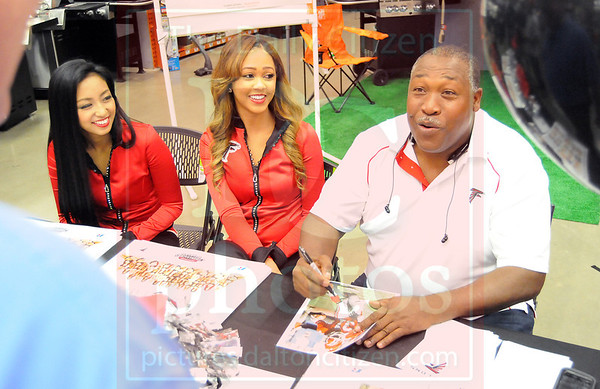 Matt Hamilton/The Daily Citizen<br /> From left, cheerleaders Rie and Ariel and former Falcons player William Andrews sign autographs and talk with fans at Home Depot Thursday.