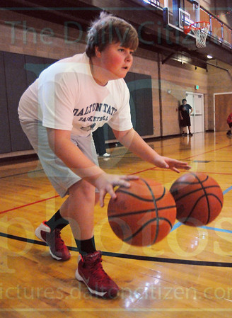 Matt Hamilton/The Daily Citizen<br /> Will Rowland, 13, dribbles two basketballs during a basketball camp at First Presbyterian Church Friday.
