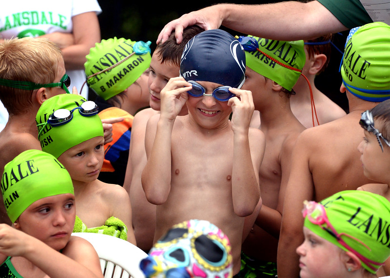 Elias Panachyda, center, wears a Penn State swimming cap amid Lansdale Swim Club green as the 8-and-under swimmers get organized for their home meet with Hatfield June 25, 2015.<br /> Bob Raines--Montgomery Media