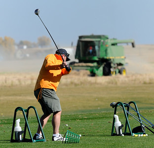 Nanton. Alta - Sept. 30, 2012 - Golfers and farmers have taken full advantage of the warm dry weather during the month of September to work hard and play hard. Paul Wyke hits balls on the driving range before playing a round of golf at the Nanton Golf Club as combines harvest canola nearby. (Mike Sturk photo)