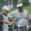 Vijay Singh and his caddies checking the manual on the yardage.