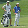 Richard Lee and his caddie waiting for the group ahead of them to clear the green.