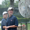 Two young men enjoying the cool mister provided at the tournament for people to coll off in.