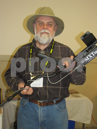 Greg Gust of Greg's Treasure Recoveries holds one the metal detectors he has on display and for sale.