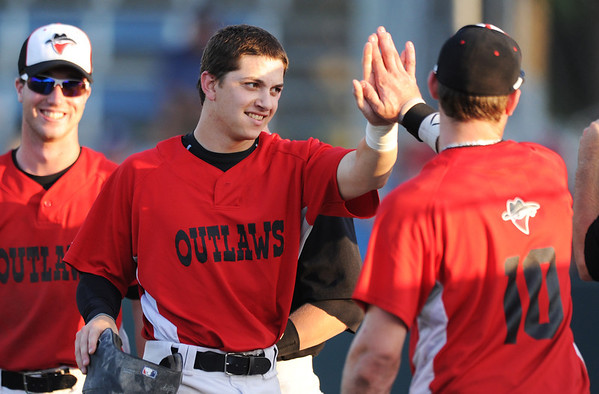 Globe/T. Rob Brown<br /> Outlaws runner Enrique Finol celebrates with teammate Alex Wise (10) at the dugout after scoring a run against Chillicothe Wednesday evening, June 19, 2013, at Joe Becker Stadium.