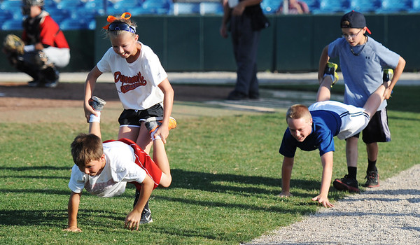 Globe/T. Rob Brown<br /> Siblings Darcy, 11, and Cy Darnell, 8, (left) take a controlling lead in the human wheelbarrow race against friends Zack Carey, 11, and Josh Scheuermann, 10, all four children from Webb City, during the third inning of the Outlaws baseball game against the St. Joseph Mustangs Monday evening, June 10, 2013, at Joe Becker Stadium in Joplin.