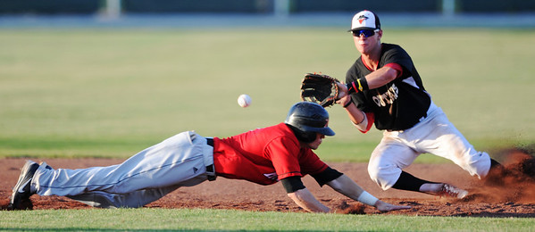 Globe/T. Rob Brown<br /> Outlaws infielder Gordon Guild reaches out for the ball as St. Joseph Mustangs runner Michael Schulze slides toward second base Monday evening, June 10, 2013, at Joe Becker Stadium. The runner was called safe on the play.