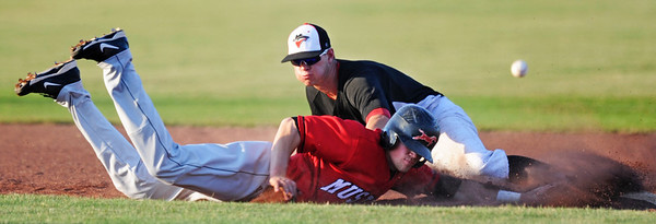 Globe/T. Rob Brown<br /> Outlaws infielder Gordon Guild loses control of the ball as St. Joseph Mustangs runner (the shortstop #7) slides toward second base Monday evening, June 10, 2013, at Joe Becker Stadium. The runner was called safe on the play.