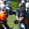 Denver Broncos quarterback Peyton Manning, right, hands the ball of to Broncos running back Willis McGahee (23) during minicamp at the NFL team's football training facility in Englewood, Colo., on Monday, May 21, 2012. (AP Photo/Ed Andrieski)