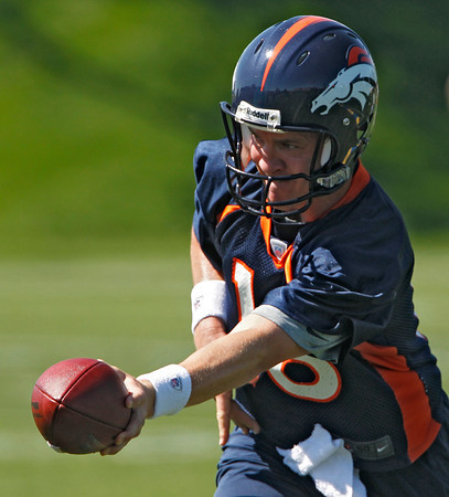 Denver Broncos quarterback Peyton Manning (18) hands the ball off during minicamp at the NFL team's football training facility in Englewood, Colo., on Monday, May 21, 2012. (AP Photo/Ed Andrieski)