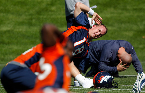 Denver Broncos quarterback Peyton Manning stretches during the team's minicamp at Broncos headquarters in Englewood, Colo., on Monday, May 21, 2012. (AP Photo/David Zalubowski)