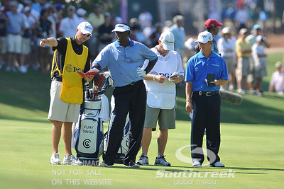 Vijay Singh listems to his caddie while David Toms waits in the background on Thursday during the first round of the PGA Championships at the Atlanta Athletic Club in Johns Creek, GA.