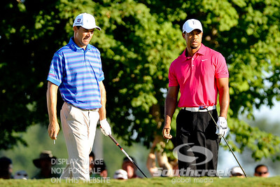 Tiger Woods continues to watch his drive as Padraig Harrington walks towards the tee box to tee off on Thursday during the first round of the PGA Championships at the Atlanta Athletic Club in Johns Creek, GA.