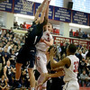 Central Catholic's Nick Cambio blocks a last second shot attempt by St. John's Prep player Mike Bisson during their game in Lawrence.