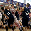 St. Johns Prep player Mike Bisson pulls down a rebound ahead of Central Catholic's Nick Cambio.