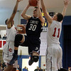 St. John's Prep player Max Burt drives to the basket between Central Catholic defenders Alex Santos, left, and Tyler Nelson (11).