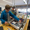RYAN HUTTON/ Staff photo. <br /> Nicholas Berube, 14, left, fits a plexiglass cover over the electronics of the Whittier Tech robotics team's robot as teammate Grant Montecalro, 15, looks on.
