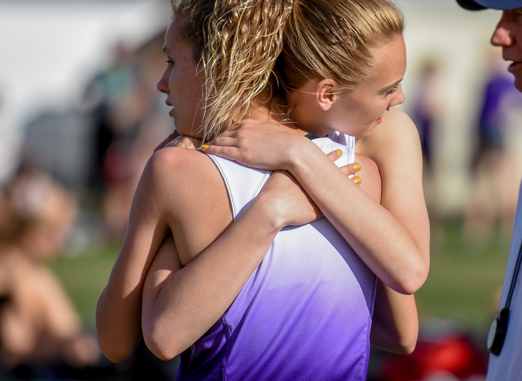 . Mountain View teammates Chloe Miller, right, and Laurene Powell hug after the high jump competition during the R2J Meet on Thursday April 12, 2018 at LHS. (Cris Tiller / Loveland Reporter-Herald)