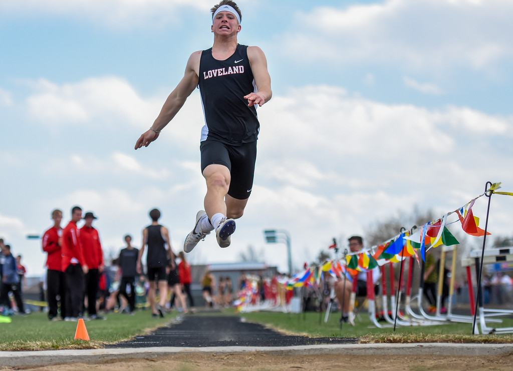 . Loveland\'s Zach Weinmaster soars through the air toward the long jump pit during the R2J Meet on Thursday April 12, 2018 at LHS. (Cris Tiller / Loveland Reporter-Herald)