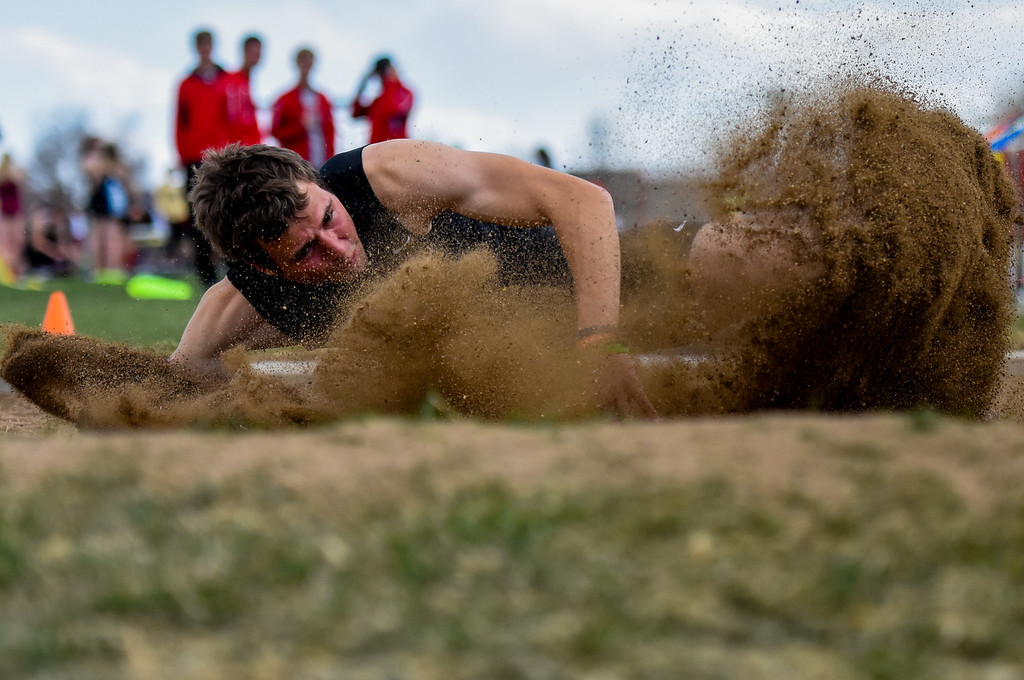 . Berthoud\'s Ryan Schmad splashes the sand of the long jump pit during the R2J Meet on Thursday April 12, 2018 at LHS. (Cris Tiller / Loveland Reporter-Herald)