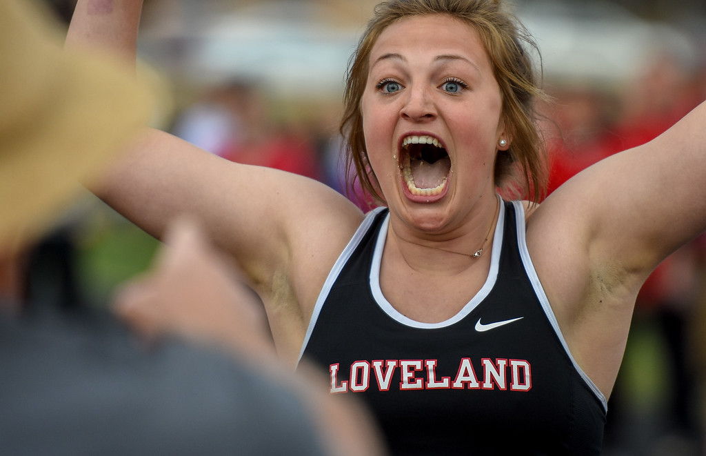 . Loveland\'s Moira Dillow celebrates after winning the girls 4x50 meter relay, which involved finishing an entire banana to win the exhibition event during the R2J Meet on Thursday April 12, 2018 at LHS. (Cris Tiller / Loveland Reporter-Herald)