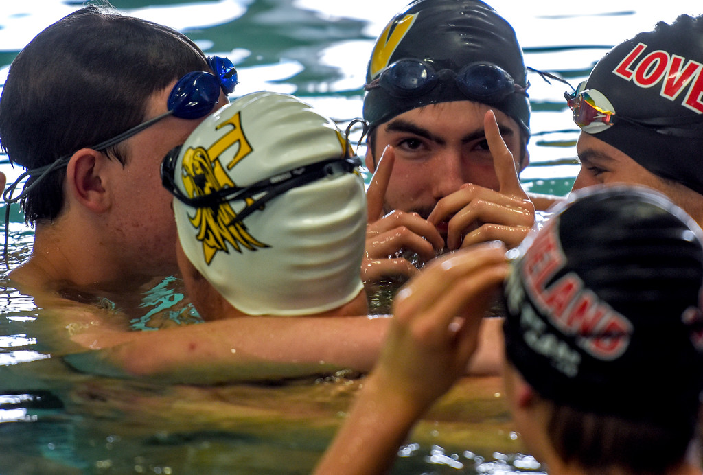 . Loveland and Thompson Valley swimmers huddle up in warmups during the City Swim Meet on Wednesday April 11, 2018 at the MVAC. (Cris Tiller / Loveland Reporter-Herald)