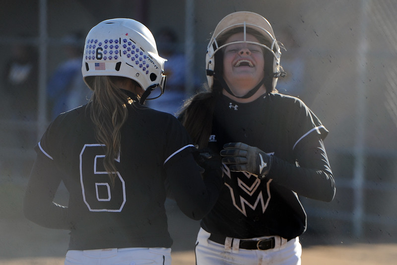 Mountain View's Kendall Petty, right, shares a laugh with Morgan Jewell after an awkward slide during their game Thursday, Oct. 4, 2018 at Mountain View High School. (Sean Star/Loveland Reporter-Herald)