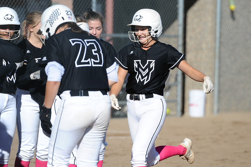 Mountain View's Kamryn Leoffler is greeted at home plate after a home run during a game Thursday, Oct. 4, 2018 at Mountain View High School. (Sean Star/Loveland Reporter-Herald)