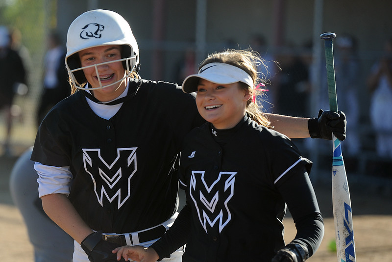 RaLeigh Basart, left, puts her arm around Morgan Jewell after hitting a home run during their game Thursday, Oct. 4, 2018 at Mountain View High School. (Sean Star/Loveland Reporter-Herald)