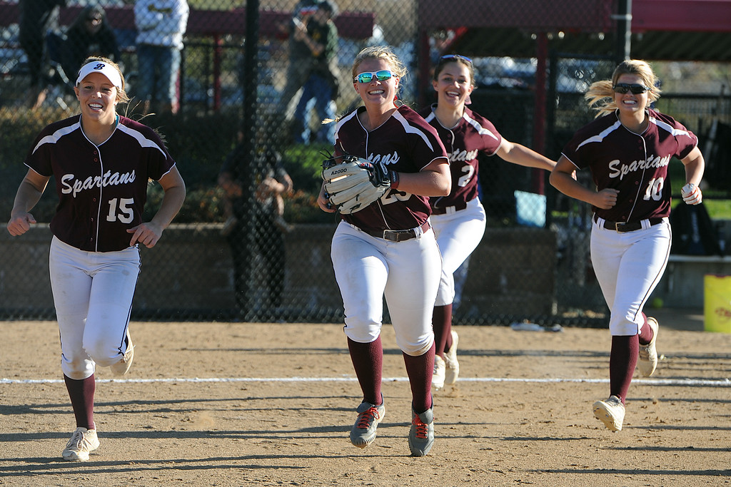 . From left, Berthoud\'s Addi Spears, Sarah Jorissen, Sophie Supernor and Carly Rafferty celebrate their win over No. 1 Pueblo County at 4A state softball tournament on Friday, Oct. 19, 2018 at Aurora Sports Park. (Sean Star/Loveland Reporter-Herald)
