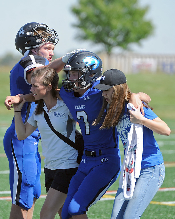 . Resurrection Christian\'s Buck Coors (7) gets a pat on the helmet from teammate Zane Zuhlke as he heads to the sideline with help from the Cougars\' training staff during a game against The Classical Academy on Saturday, Sept. 15, 2018 at Loveland Sports Park. (Sean Star/Loveland Reporter-Herald)
