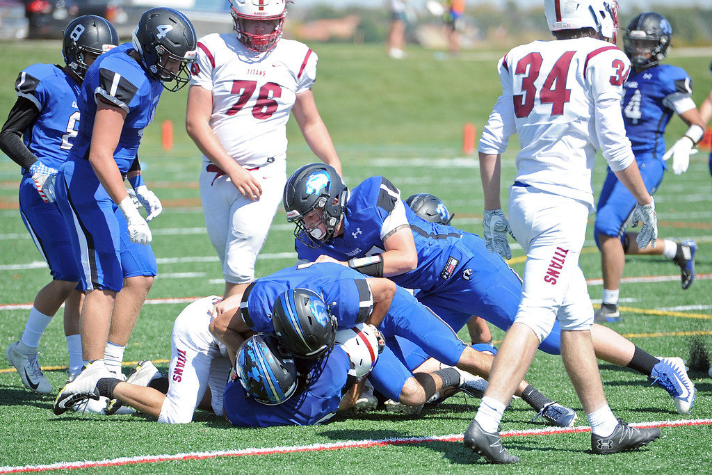 . A trio of Resurrection Christian defenders take down the ball carrier during a game against The Classical Academy on Saturday, Sept. 15, 2018 at Loveland Sports Park. (Sean Star/Loveland Reporter-Herald)