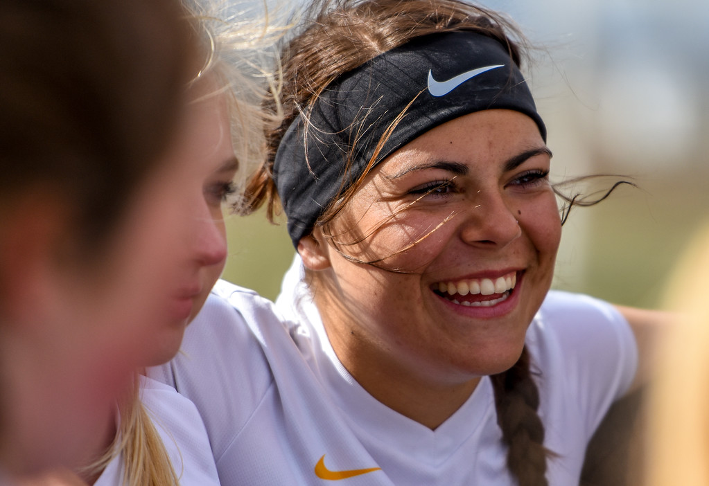 . Thompson Valley\'s Kylea Wall smiles in a huddle before a match against crosstown rival Mountain View on Tuesday April 17, 2018 at MVHS. (Cris Tiller / Loveland Reporter-Herald)