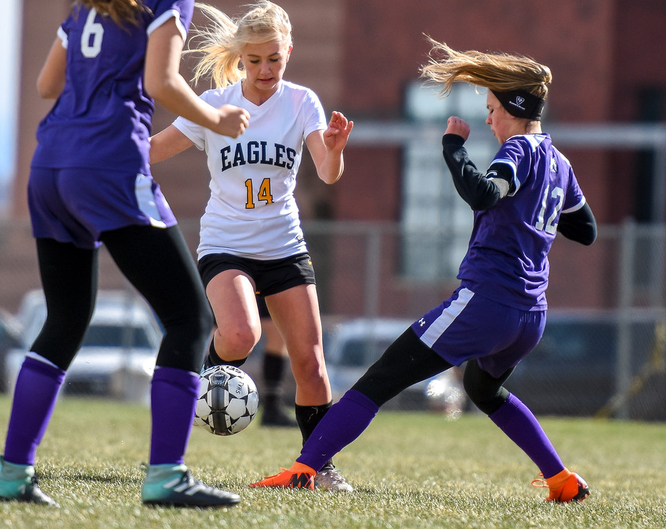 . Thompson Valley\'s Novi Briggs (14) dribbles between defenders against crosstown rival Mountain View on Tuesday April 17, 2018 at MVHS. (Cris Tiller / Loveland Reporter-Herald)