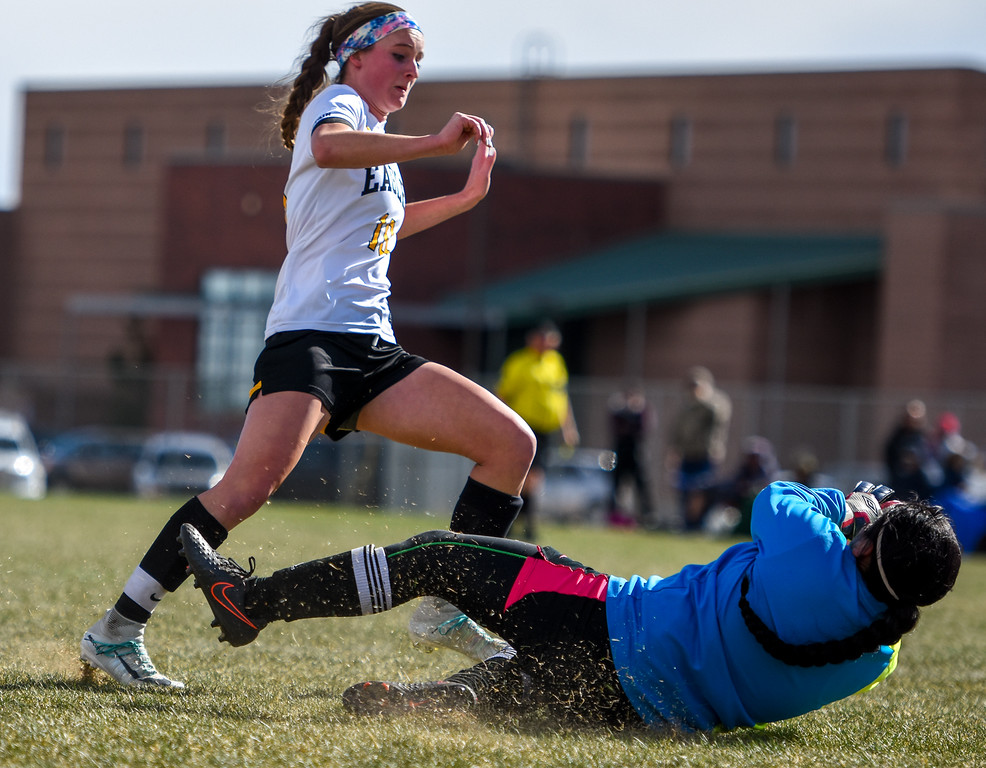 . Mountain View keeper Beatriz Lopez, right, slides into a save in front of Thompson Valley\'s Kahrena Thompson on Tuesday April 17, 2018 at MVHS. (Cris Tiller / Loveland Reporter-Herald)