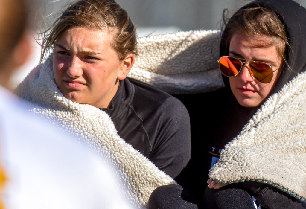. Thompson Valley players huddle up under a blanket to hide from the wind against crosstown rival Mountain View on Tuesday April 17, 2018 at MVHS. (Cris Tiller / Loveland Reporter-Herald)