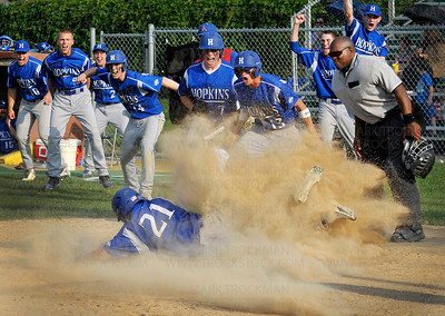 Royals first baseman, junior Joe Brettingen (21), slides safely into home plate amidst the cheerful uproar of his exuberant teammates in the fifth inning against Robbinsdale Armstrong Tuesday, June 7, at Parade Stadium in Minneapolis.  Playing in the Section 6 losers bracket, Hopkins creamed the Falcons 15-5 in six innings.
