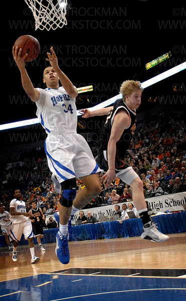 Hopkins senior Trent Lockett, left, stays calm in a chaotic scene at the Target Center in the state semifinals on Thursday, March 26.  Lockett scored seven points as the Royals defeated St. Cloud Tech 55-36.