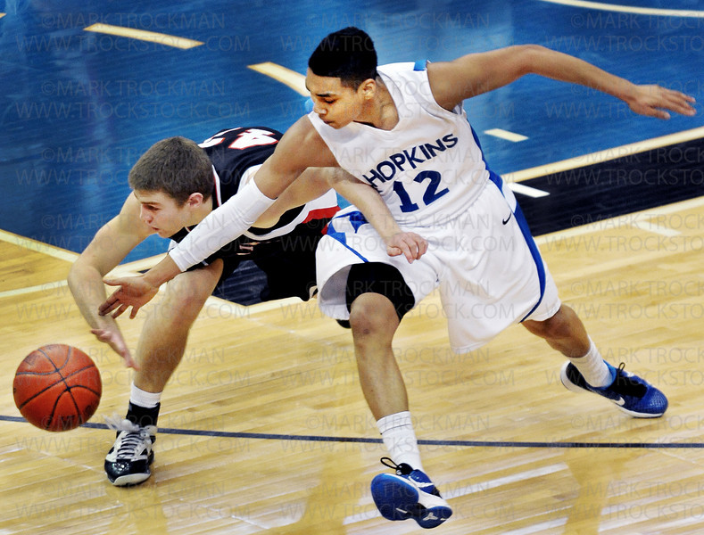 Hopkins junior guard Demetrius Martin (12) chases after a loose ball with Eden Prairie forward Jacob Foss in the second half of the Royals 64-52 Class 4-A state championship victory over the Eagles Saturday, Mar. 26, at Target Center in Minneapolis.