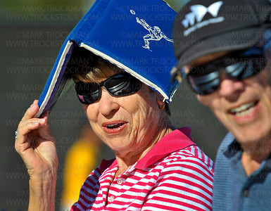 Carol Musser, left, sitting next to her husband Kent, shades herself from the hot afternoon sun at Hopkins High School's tennis courts Thursday, Sept. 13, in Minnetonka.  The Kents were cheering for their granddaughter, Royals player Mattie Johnson, during the Lake Conference match.