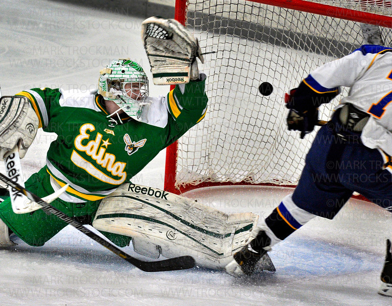 Wayzata senior forward Akash Batra, right, scores on Edina goaltender Willie Benjamin in the first period, Saturday Jan. 26, at Plymouth Ice Center.  The Hornets won their Lake Conference duel, beating the Trojans 5-4.
