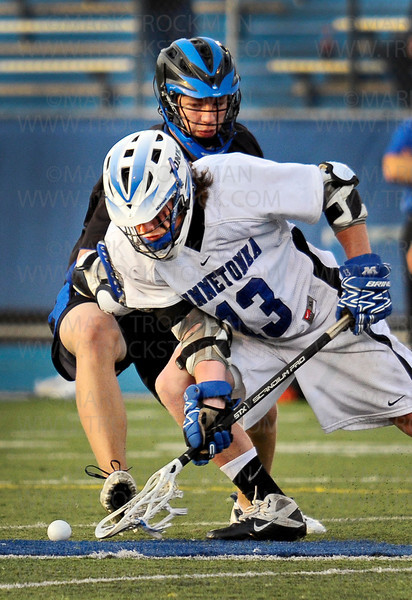 Tonka senior middie Connor Gatenby (13) scrapes up a loose ball in the first half of Minnetonka's 16-4 whooping of their Lake Conference foes Thursday, May 19, at Minnetonka High School.