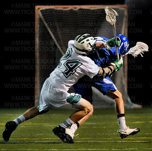 Skippers sophomore midfielder Matthew Boyce, right, is hit from behind by Hornets midfielder Ted Goltzman in the first half of Minnetonka's 7-5 defeat of conference rival Edina Tuesday, May 15, at Edina Community Center.