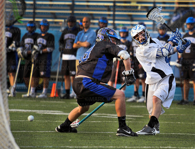 Skippers junior attacker Teddy O'Reilly, right, let's one fly past Hopkins denfenseman Daniel George Thursday, May 19, at Einer Anderson Stadium on the Minnetonka High School Campus.  Minnetonka crushed their Lake Conference rivals 16-4, with O'Reilly scoring five goals in the match.