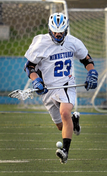 Tonka senior middie Parker Weinstock (23) concentrates on a loose ball in the first half of Minnetonka's 16-4 whooping of their Lake Conference foes, Hopkins, Thursday, May 19, at Minnetonka High School.<br /> <br /> <br /> <br /> <br /> Skippers junior attacker Teddy O'Reilly, right, let's one fly past Hopkins denfenseman Daniel George Thursday, May 19, at Einer Anderson Stadium on the Minnetonka High School Campus.  Minnetonka crushed their Lake Conference rivals 16-4, with O'Reilly scoring five goals in the match.