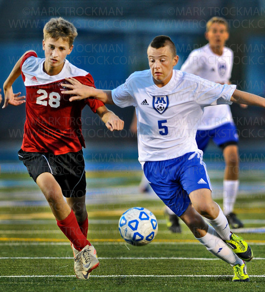 Skippers freshman midfielder Suad Suljic (5) battles for control of the ball with Coon Rapids defenseman Ryan Nelson in first-half action at Einer Anderson Stadium Saturday, Sept. 15, in Minnetonka.  Suljic scored Tonka's only goal, on a penalty kick, in the Skippers 2-1 loss to the Cardinals.