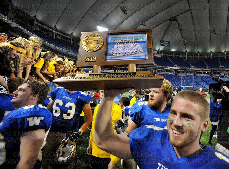 Trojan senior Tucker Kline hoists the class 5A championship trophy for their fans to see after beating Rosemount 31-14 Friday, Nov. 27, at the Metrodome in MInneapolis.