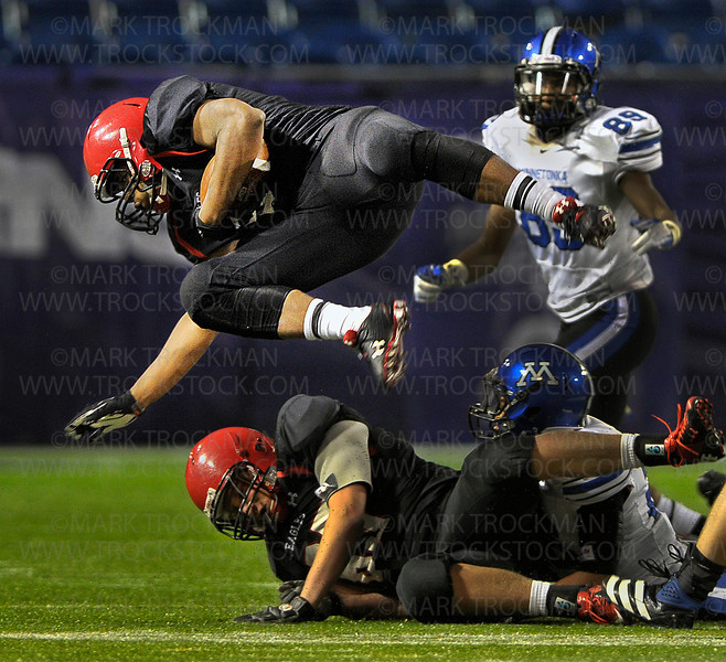Eagles junior Anthony Anderson, top, is tripped up by Minnetonka junior free safety Anthony Tatum, bottom right, in a tight state tournament quarterfinal game Friday, Nov. 9, at the Metrodome in Minneapolis.  Eden Prairie topped the Skippers 21-18.