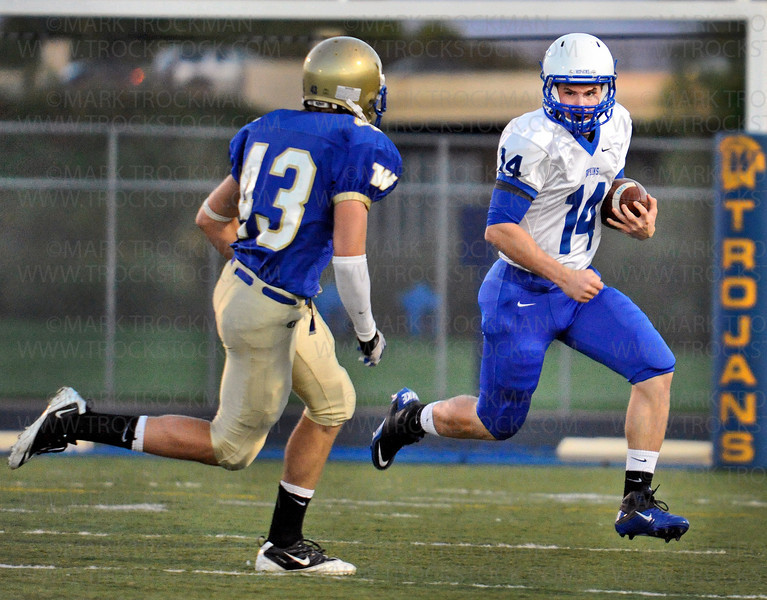 Hopkins senior quarterback Bill Gregg (14) is chased by Wayzata linebacker Colin Lindquist early in the Trojans 35-14 win against the Royals Friday, Sept. 24, 2010, in Lake Conference action at Wayzata.