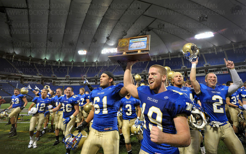 Trojan senior Tucker Kline hoists the class 5A championship trophy along with his teammates after beating Rosemount 31-14 for the class 5A championship Friday, Nov. 27, at the Metrodome in MInneapolis.